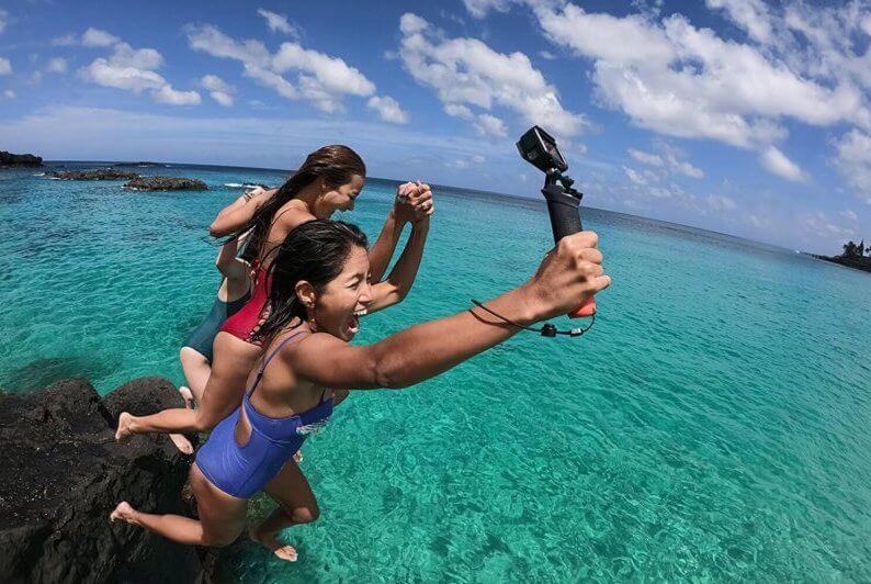 GoPro用ハンドグリップを持って海に飛び込む女性