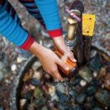 防水ビデオカメラを水道で洗っている
