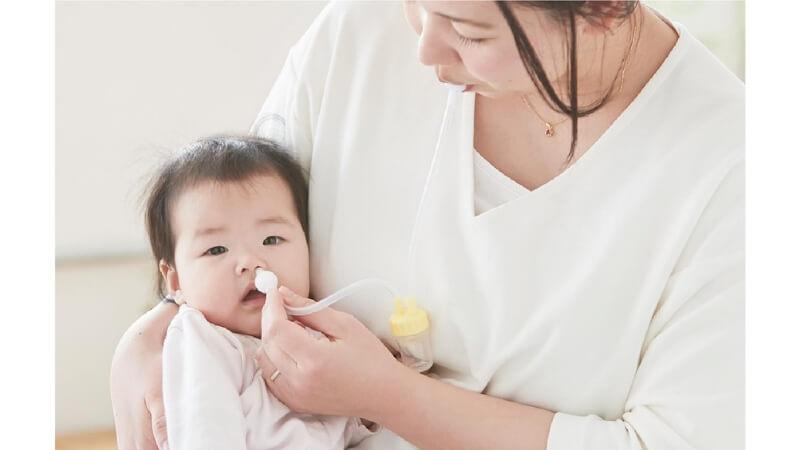 鼻水すい器で鼻水を取るママ